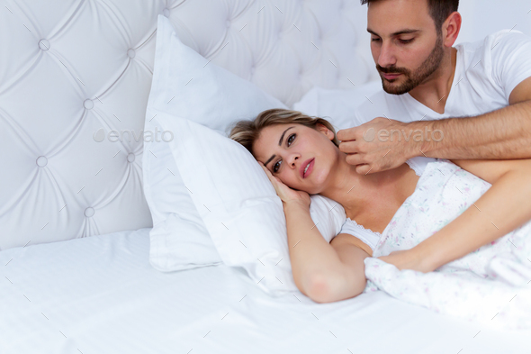 Portrait of unhappy young couple in bedroom - Stock Photo - Images
