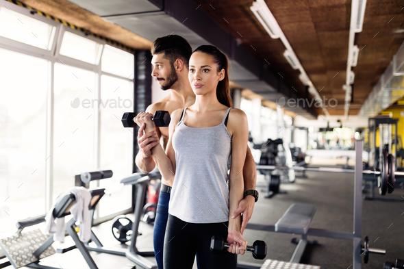 Young sexy woman doing exercises in gym with trainer - Stock Photo - Images