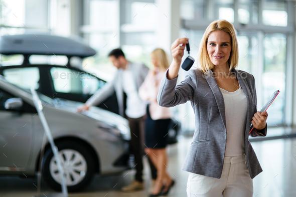 Portrait of beautiful saleswoman standing inside vehicle showroom - Stock Photo - Images