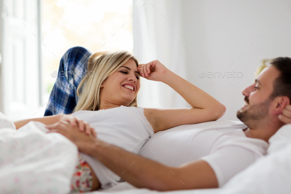 Happy couple enjoying their time in bed - Stock Photo - Images