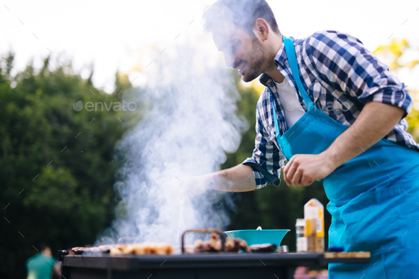 Handsome male preparing barbecue - Stock Photo - Images