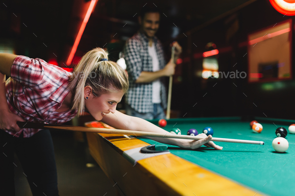 Young attractive woman playing pool in bar - Stock Photo - Images