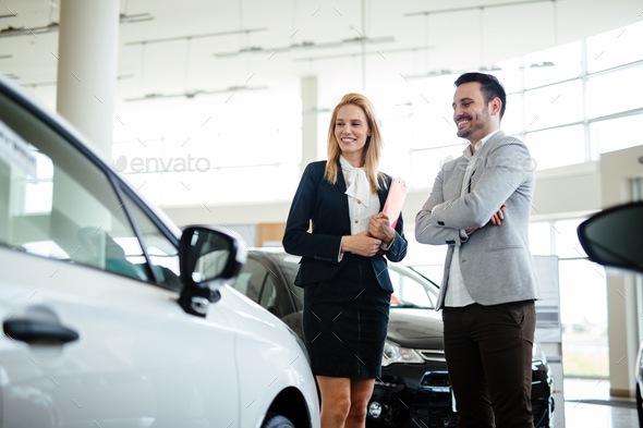 Young female car sales consultant working in showroom - Stock Photo - Images