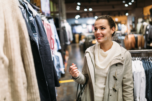 Young attractive woman buying clothes in mall - Stock Photo - Images