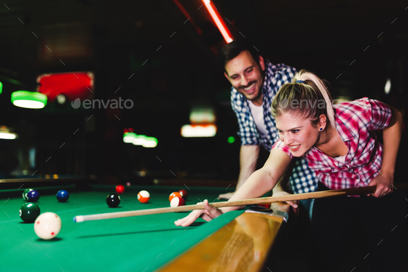 Young couple playing snooker together in bar - Stock Photo - Images
