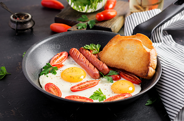 English breakfast - fried egg,  tomatoes, sausage,  and toasts. Top view - Stock Photo - Images
