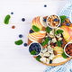 Cheese platter with assorted cheeses, blueberry, apples, nuts on white table. - PhotoDune Item for Sale