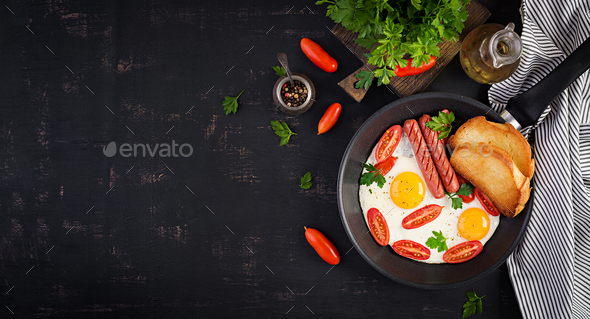 English breakfast - fried egg,  tomatoes, sausage,  and toasts. Banner. Top view, overhead - Stock Photo - Images