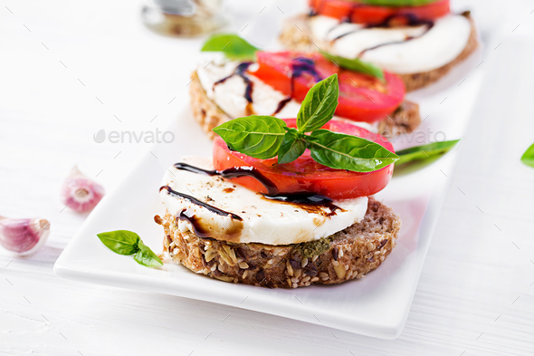 Sandwiches with mozzarella, tomatoes and rye bread on white wooden table. - Stock Photo - Images
