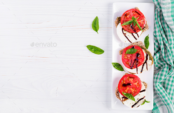 Sandwiches with mozzarella, tomatoes and rye bread on white wooden table. Top view - Stock Photo - Images