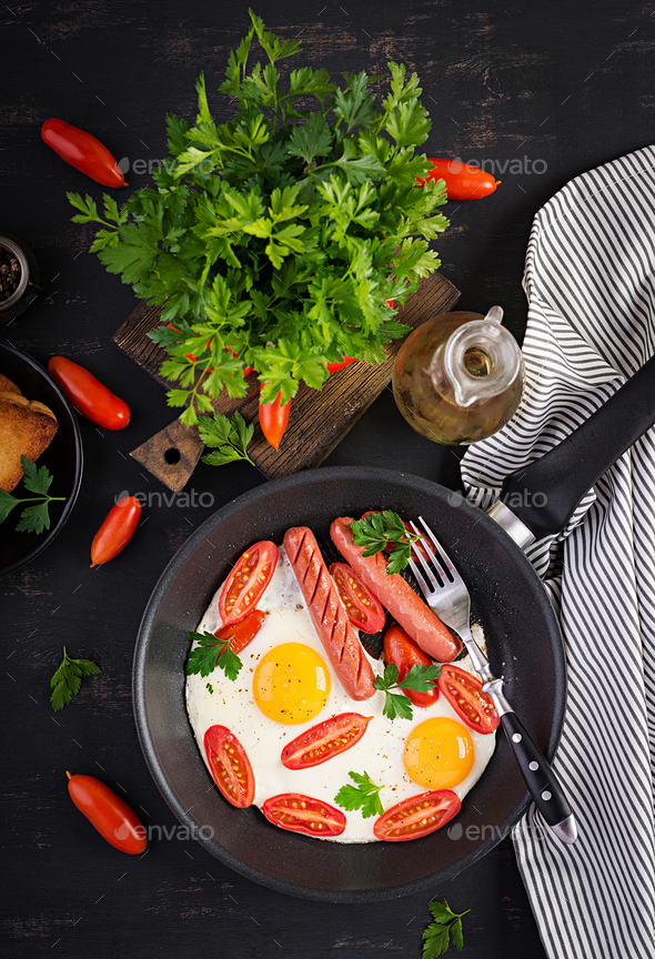 English breakfast - fried egg,  tomatoes, sausage,  and toasts. Top view, overhead - Stock Photo - Images