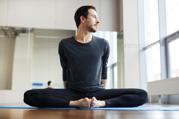 Flexible man sitting inbound angle pose - Stock Photo - Images