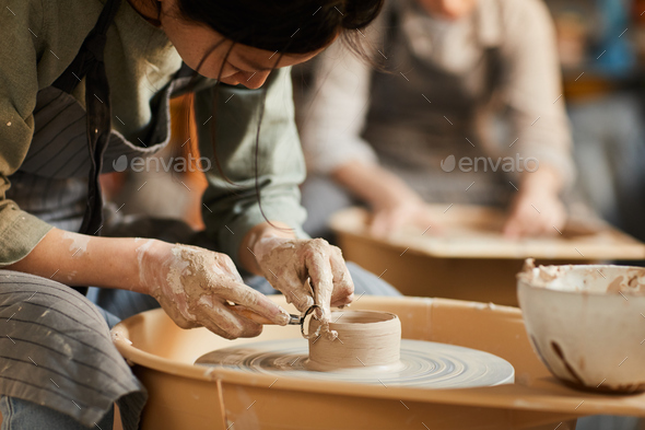 Shaping wet clay on pottery wheel - Stock Photo - Images
