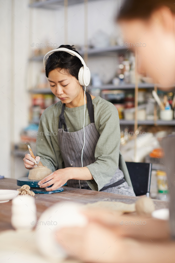 Asian woman shaping bottom of bowl - Stock Photo - Images