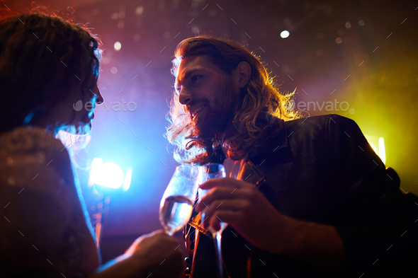 Hipster guy talking to charming lady in nightclub - Stock Photo - Images