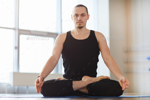Muscled young man meditating alone - Stock Photo - Images