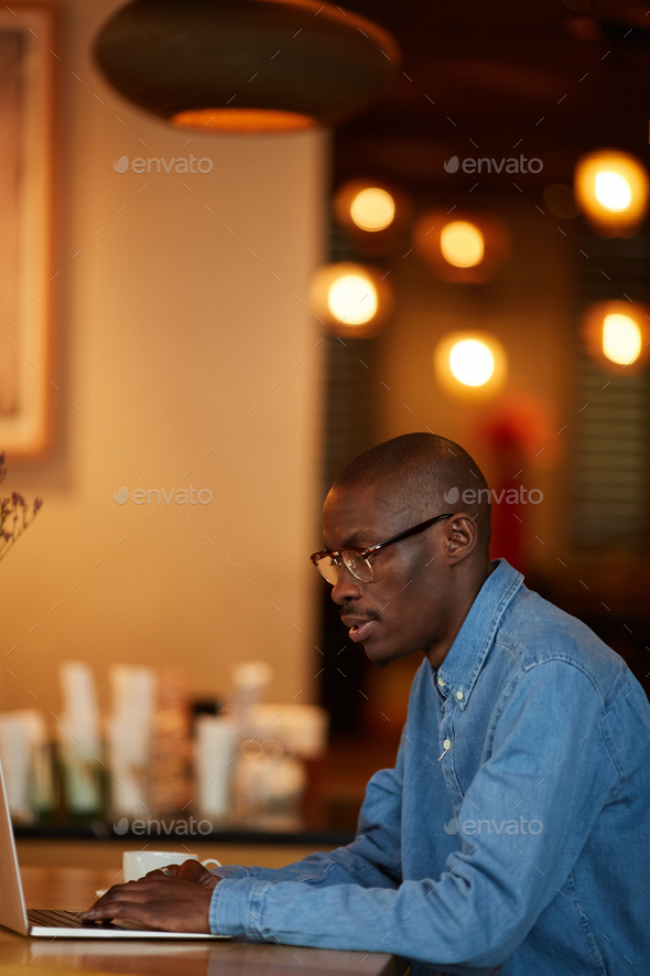 African Man Working with Laptop in Cafe - Stock Photo - Images