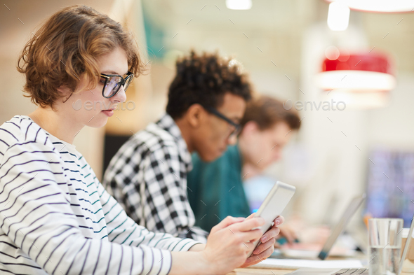 Thoughtful student girl using tablet in university - Stock Photo - Images