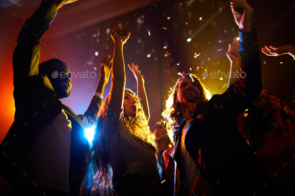 Excited people dancing at concert in nightclub - Stock Photo - Images