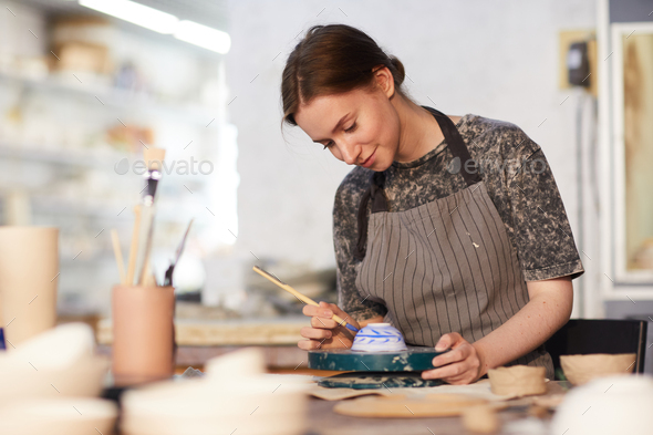 Skilled lady drawing on ceramic bowl - Stock Photo - Images