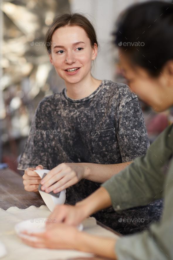 Craftswomen talking while working - Stock Photo - Images