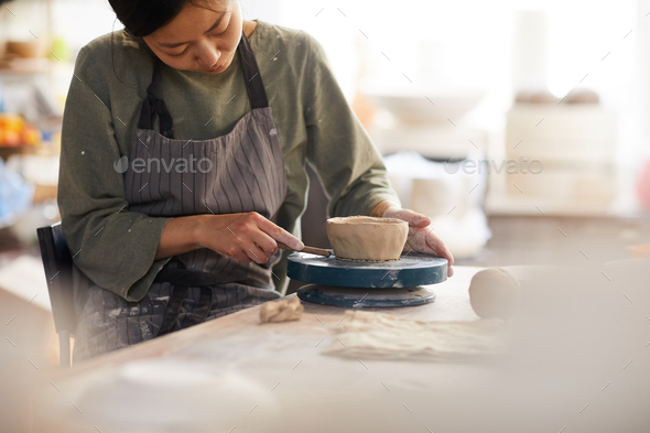Young woman using cutter while making bowl - Stock Photo - Images
