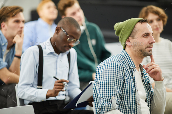Pensive multiethnic students at conference - Stock Photo - Images