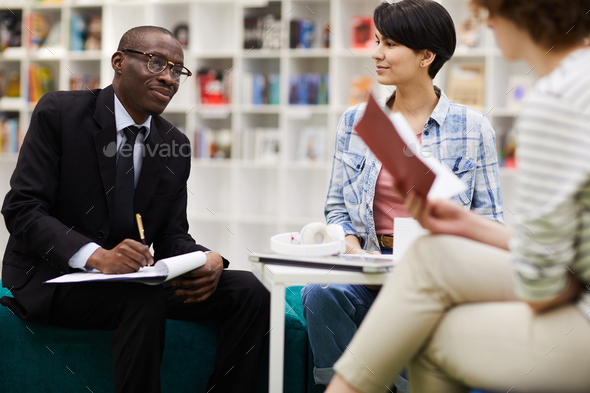 Students talking to investor at meeting - Stock Photo - Images