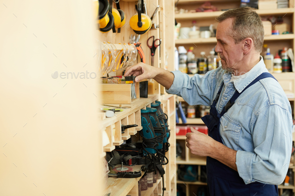 Senior Carpenter Choosing Tools - Stock Photo - Images