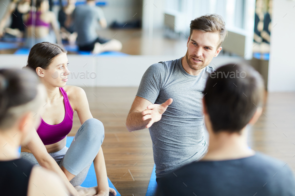 Sporty guy sharing ideas at yoga class - Stock Photo - Images