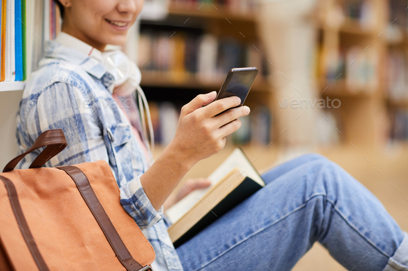 Texting sms in library - Stock Photo - Images