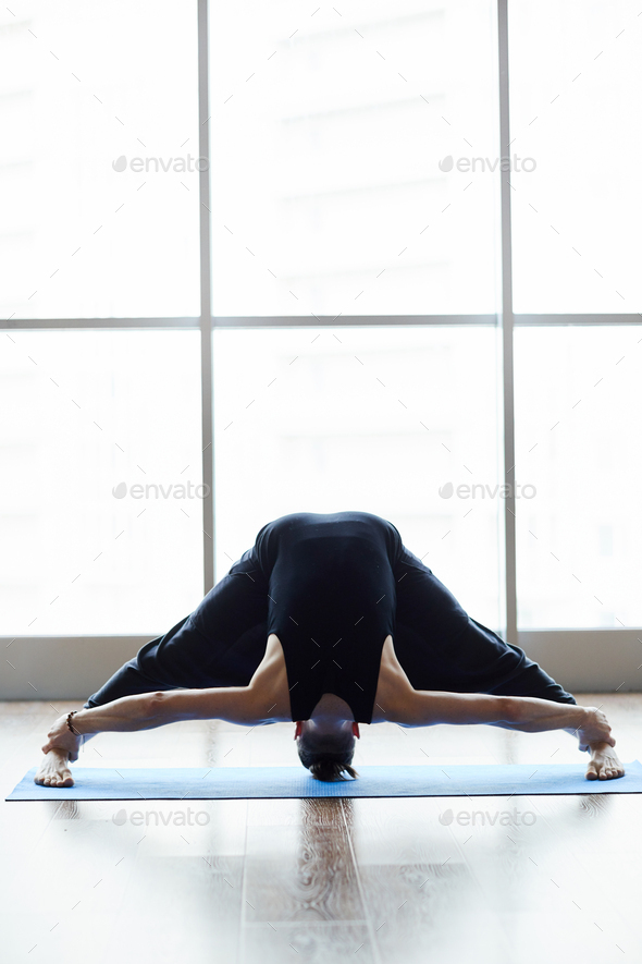 Wide-legged standing forward bend - Stock Photo - Images