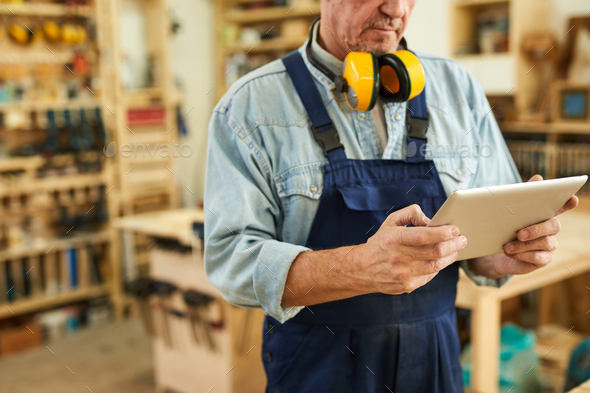 Senior Carpenter using Tablet - Stock Photo - Images