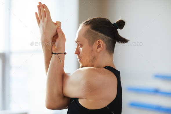 Yoga pose including eagle arms - Stock Photo - Images