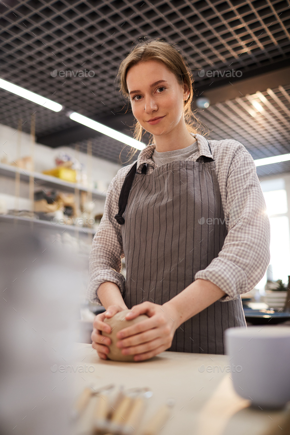 Attractive lady kneading clay - Stock Photo - Images