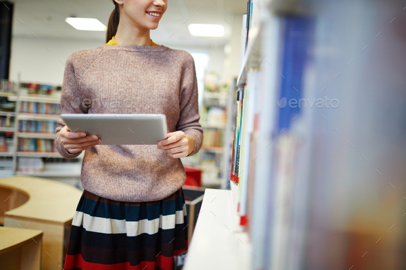 Student by bookshelf - Stock Photo - Images