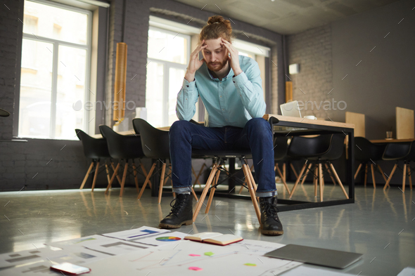 Puzzled Businessman Looking at Documents - Stock Photo - Images
