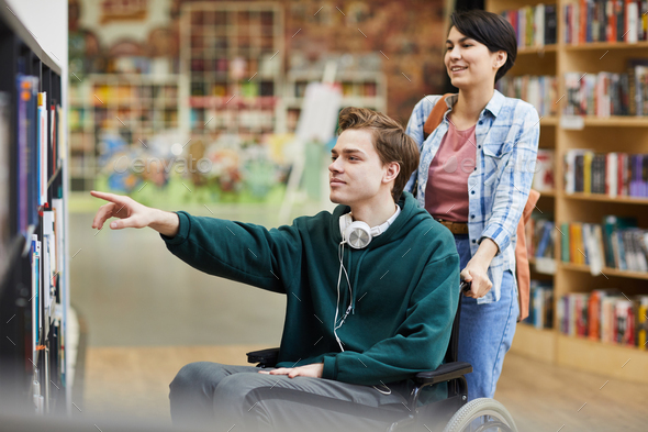 Boy in wheelchair choosing book - Stock Photo - Images