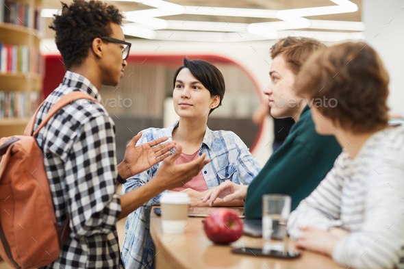 Multiethnic high school friends discussing project - Stock Photo - Images