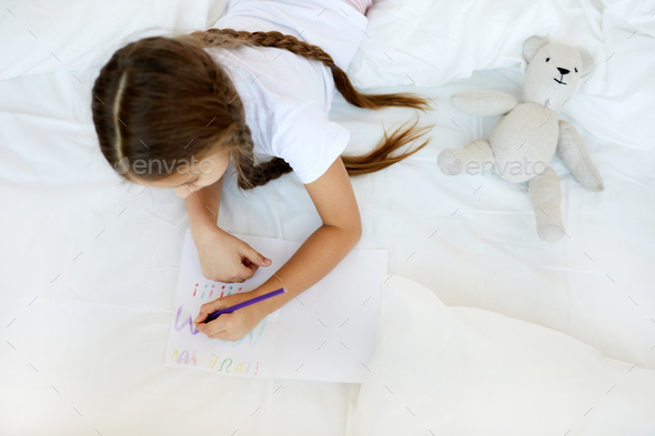 Girl Drawing in Bed - Stock Photo - Images