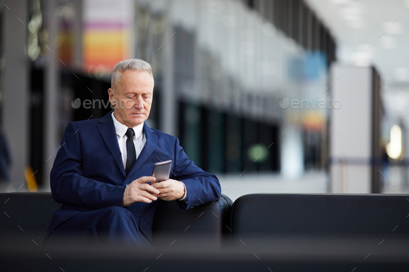 Senior Businessman Using Smartphone in Lobby - Stock Photo - Images