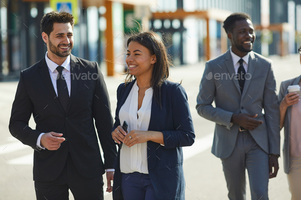 Positive multi-ethnic colleagues walking over street - Stock Photo - Images