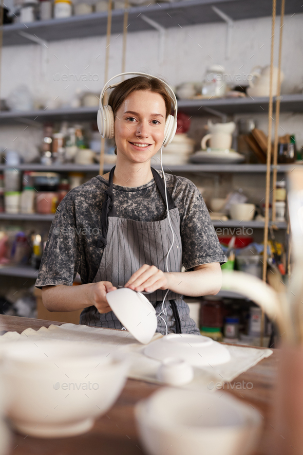 Happy potter checking crockery in workshop - Stock Photo - Images