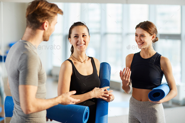 Yoga students discussing new exercises - Stock Photo - Images