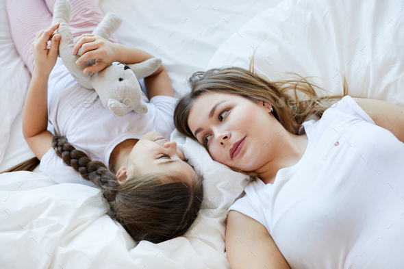 Mother and Daughter Lying on Bed - Stock Photo - Images