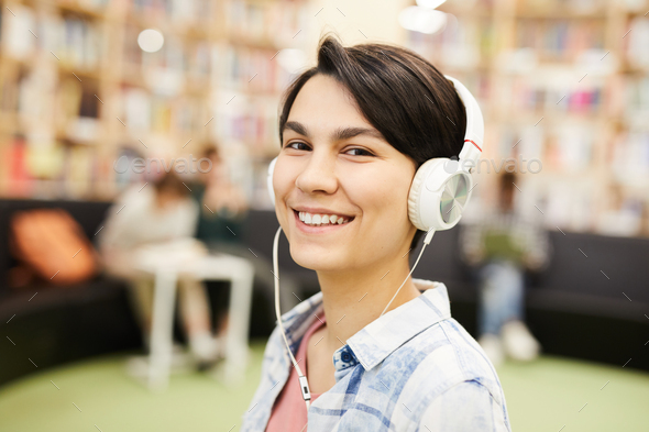 Smiling girl listening to audiobook in headphones - Stock Photo - Images