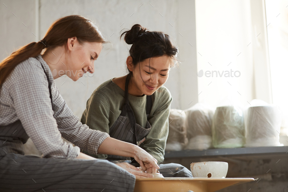 Content multi-ethnic women creating clay pot together - Stock Photo - Images