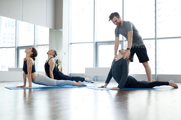 Young yoga instructor correcting cobra pose of students - Stock Photo - Images