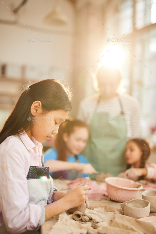 Asian Girl Shaping Clay - Stock Photo - Images