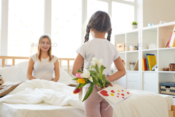 Girl Surprising Mom with Flowers - Stock Photo - Images